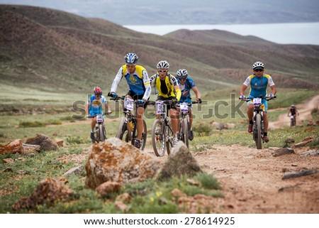"ALMATY, KAZAKSTAN - MAY 02, 2015: N.Tlegenov (N21) in action at Adventure mountain bike cross-country marathon in mountains ""Jeyran Trophy 2015""  - stock photo"