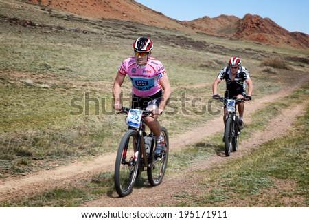 "ALMATY, KAZAKSTAN - MAY 01, 2014: R.Nurjanov (N30) in action at Adventure mountain bike cross-country marathon in mountains ""Jeyran Trophy 2014""  - stock photo"