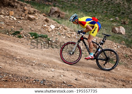 "ALMATY, KAZAKSTAN - MAY 02, 2014: S.Kovalchuk (N3) in action at Adventure mountain bike cross-country marathon in mountains ""Jeyran Trophy 2014""  - stock photo"