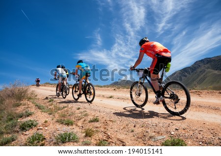 "ALMATY, KAZAKSTAN - MAY 01, 2014: Unidentified bikers in action at Adventure mountain bike cross-country marathon in mountains ""Jeyran Trophy 2014""  - stock photo"