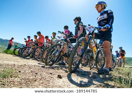 "ALMATY REGION, KAZAKHSTAN - MAY 5, 2013: N.Tlegenov (N4) and other in at the start of stage Adventure mountain bike cross-country marathon in mountains ""Jeyran Trophy 2013"".  - stock photo"