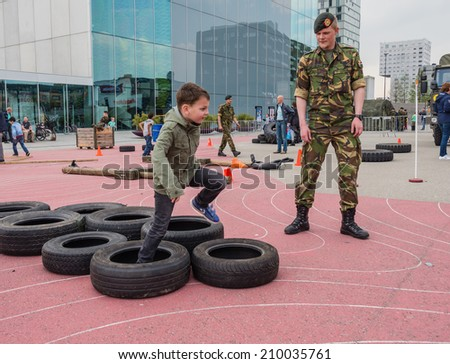 ALMERE, NETHERLANDS - 23 APRIL 2014: Children run part of a military assault course on National Army Day meant to make the public acquainted with the army - stock photo