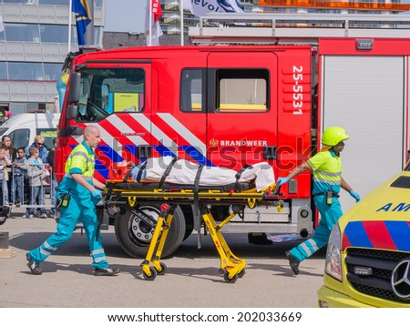 ALMERE, NETHERLANDS - 12 APRIL 2014: Firefighters and medical services at work in an enacted emergency scene during the first National Security Day held in the city of Almere - stock photo