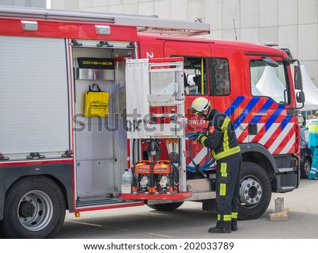 ALMERE, NETHERLANDS - 12 APRIL 2014: Firefighters at work in an enacted emergency scene during the first National Security Day held in the city of Almere - stock photo