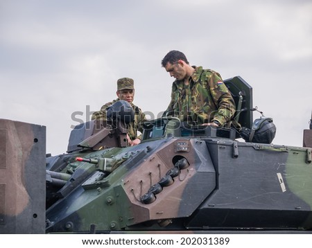 ALMERE, NETHERLANDS - 12 APRIL 2014: Soldier  climbing out through the hatch of a military  fighting vehicle on display during the first National Security Day held in the city of Almere - stock photo