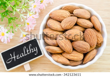 Almond and Health tag with flower on wooden background. - stock photo