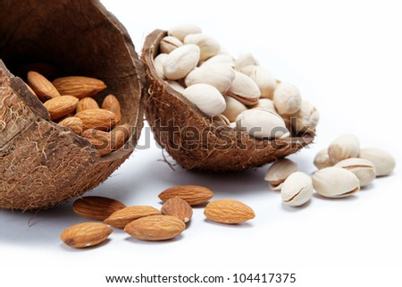 Almond and pistachio nuts in the shell of the coconut. - stock photo