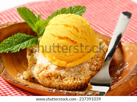 Almond cookie and scoop of ice cream served on olive wood bowl - stock photo