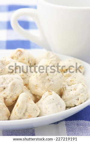 Almond cookies in white plate and white cup on checkered tablecloth. - stock photo