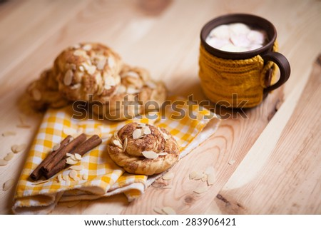 almond cookies with cup of cappucino on light wood table - stock photo