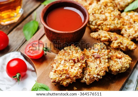 almond crusted chicken tenders with tomato sauce on dark wood background. toning. selective Focus - stock photo
