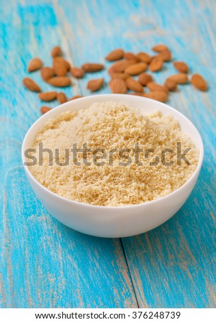 almond flour in a wooden bowl, almonds on old wooden background