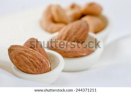 Almond in measuring spoon - stock photo