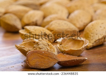 Almond kernels and its shells on wooden background - stock photo