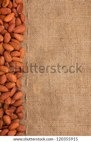 Almond lying on burlap can be used as background - stock photo