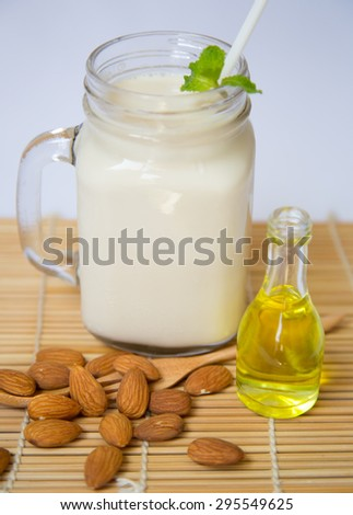 Almond Milk and Almond Seeds with Almond Oil Bottle On Wooden Table