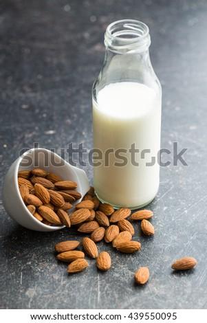 Almond milk and almonds. Tasty milk in glass bottle. - stock photo
