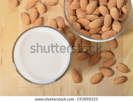 Almond milk as a substitute for dairy milk. Glass of almond milk and almonds on a wooden table. - stock photo