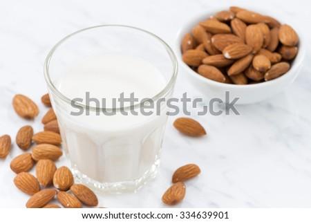 almond milk in a glass, closeup, horizontal - stock photo