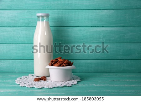 Almond milk in bottle with almonds in bowl, on color wooden background - stock photo