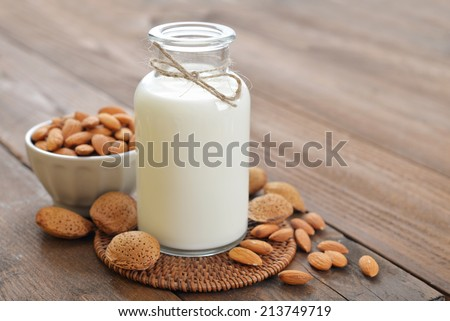 Almond milk in bottle with nuts on wooden background - stock photo