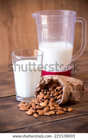 Almond milk in glass with almonds - stock photo