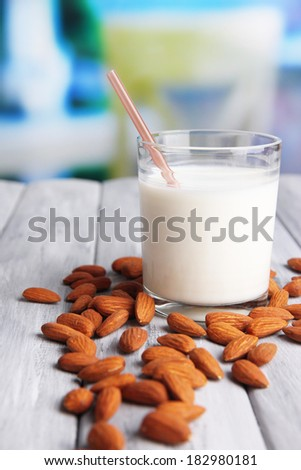 Almond milk in glass with almonds, on color wooden table, on bright background - stock photo