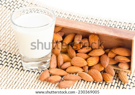 Almond milk in glass with almonds on wooden mat. - stock photo