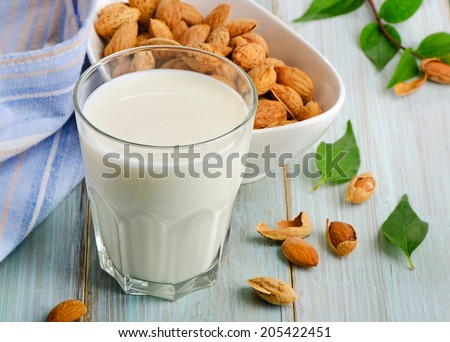 Almond milk in glass with almonds. Selective focus - stock photo