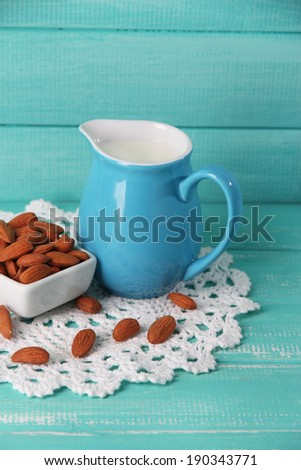 Almond milk in jug with almonds in bowl, on color wooden background - stock photo