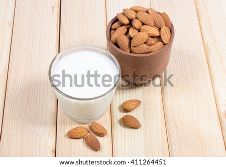 Almond milk with almond on a wooden table - vegan drink.  - stock photo