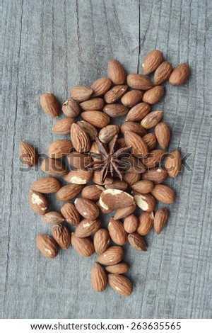 almond nut and star anise on wooden background - stock photo