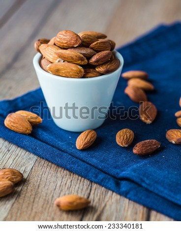 almond nuts on blue cloth on a wooden board - stock photo