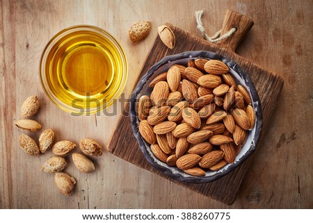 Almond oil and bowl of almonds on wooden background. Top view - stock photo