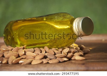 Almond oil in a bottle and almonds nuts on a wooden surface - stock photo