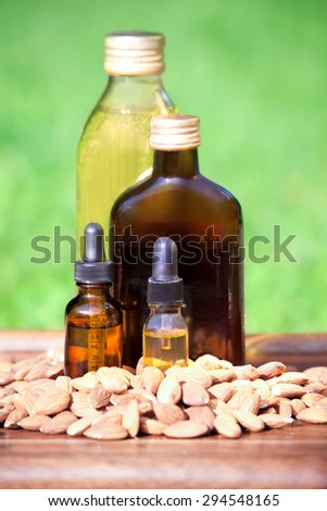 Almond oil in a bottles and almonds nuts. The concept of use of natural almond oil  in cosmetology and dietary food - stock photo