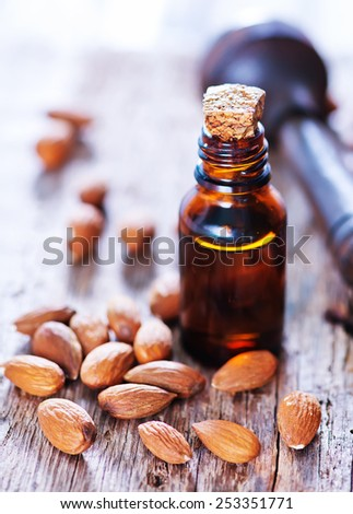 almond oil in a glass bottle with whole nuts - stock photo