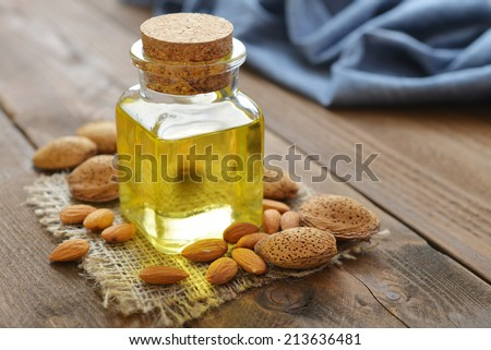 Almond oil in bottle on wooden background - stock photo