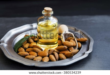 Almond oil in transparent bottle with almonds, healthy nuts oil - stock photo