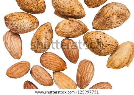 Almond seeds with shell casings and not peel on a white background.
