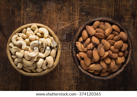Almonds and cashews in bowl on textured wooden background. Table top view food. Natural light - stock photo