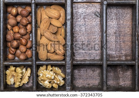 Almonds and hazelnuts in wooden bowls on wooden background - stock photo