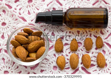 almonds and oil on pink tablecloth nuts useful products - stock photo