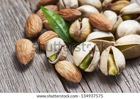 Almonds and pistachio with leaf on wooden background - stock photo
