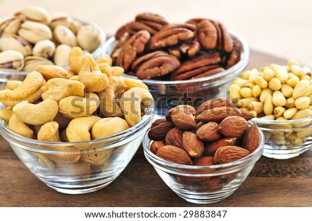 Almonds, cashews pistachio and pine nuts in glass bowls - stock photo