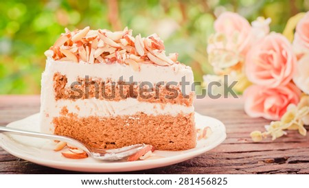 Almonds chocolate cake on wooden background soft focus vintage tone.