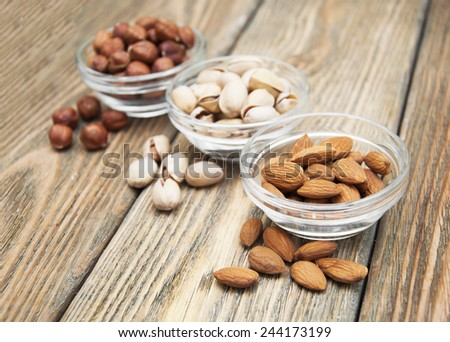Almonds, hazelnuts and pistachios in glass bowls on wooden background  - stock photo
