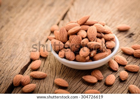 almonds in a white ceramic bowl on grained wood background - stock photo