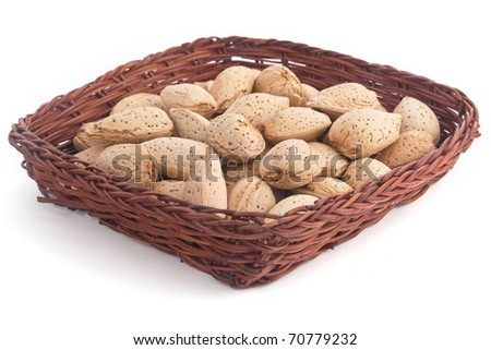 Almonds in a wicker basket - isolated on white background