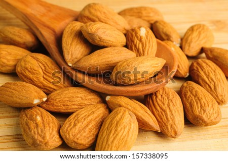 almonds in a wooden spoon on a cutting board